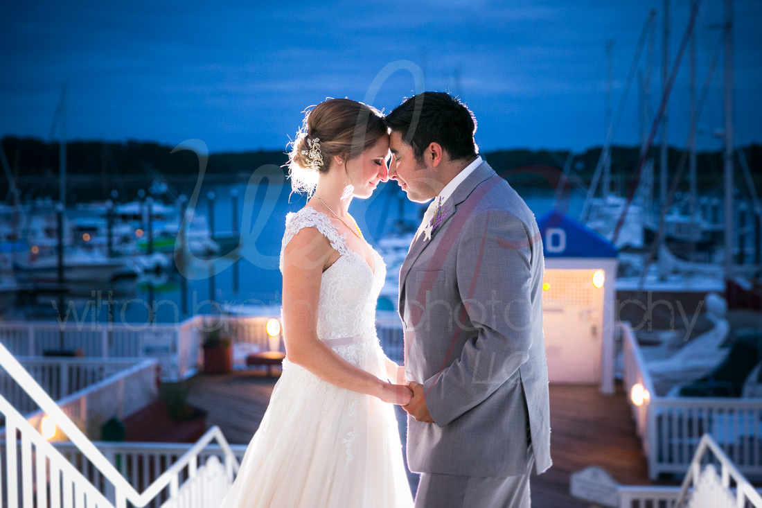 wedding couple touch foreheads at twilight at the marina