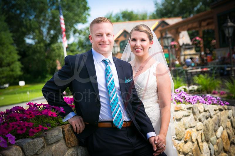Wedding couple standing on bridge smiling at camera