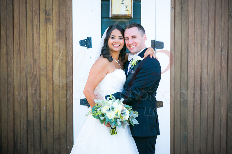 Newlyweds in front of a barn