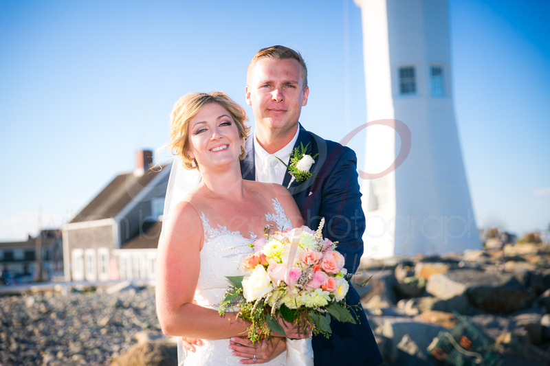 Couple in front of lighthouse on MA coast