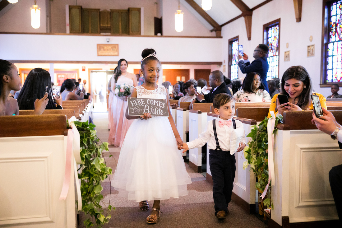 Flower girl and ring bearer carrying sign
