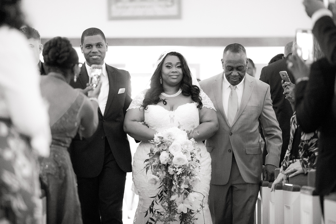Bride being escorted down the aisle in church