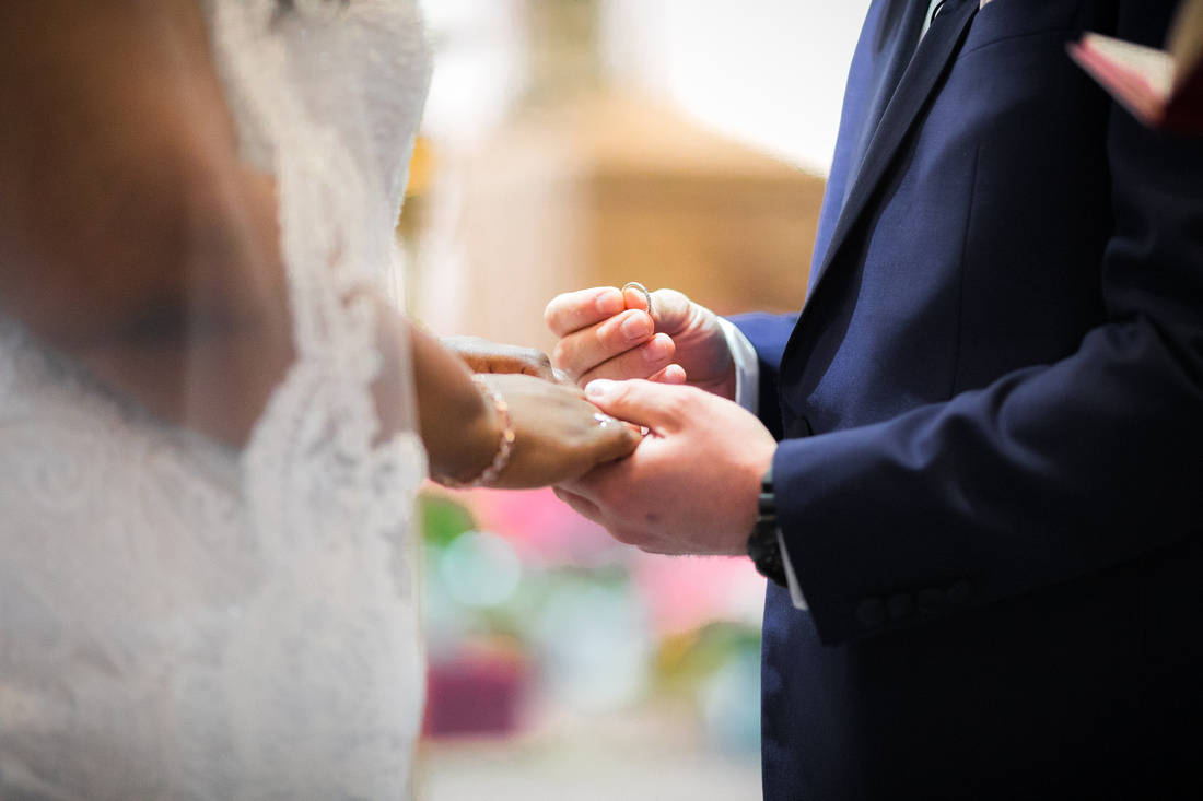 Groom putting wedding ring on finger