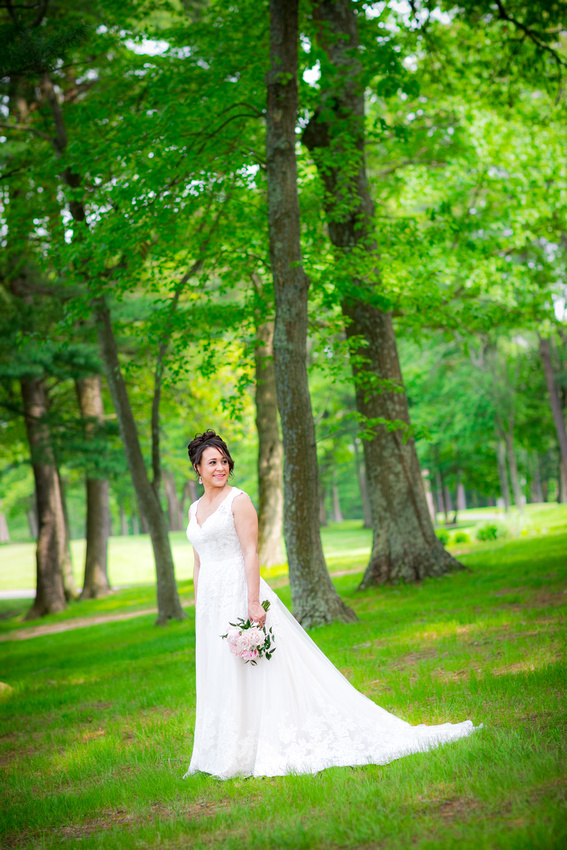 Bride stands amid trees