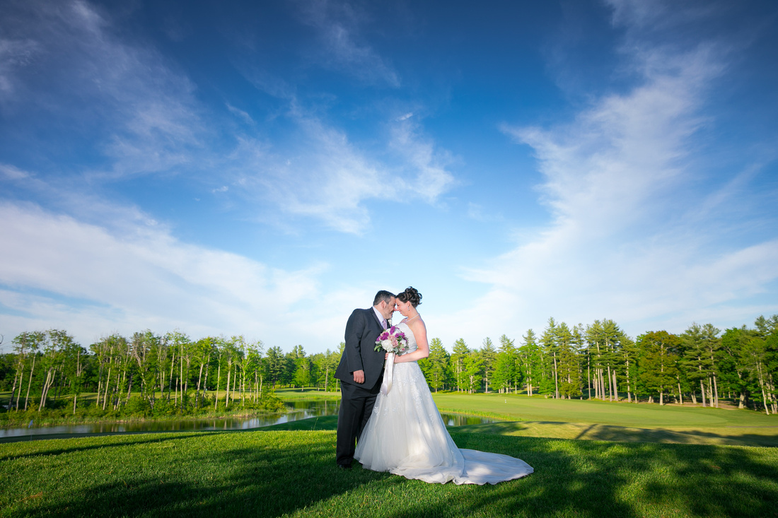 bride and groom in front of golf course