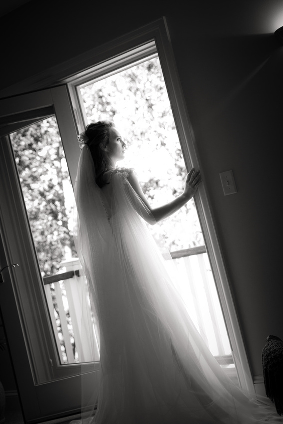 Bride stands in doorway looking out