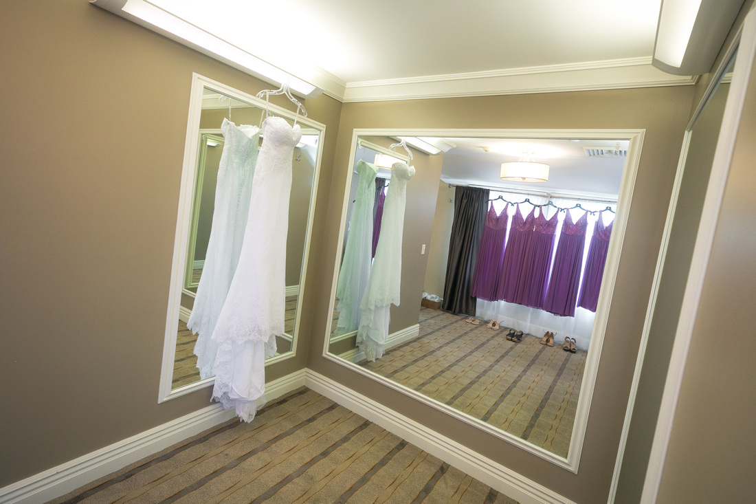 Wedding dress hanging by mirrors