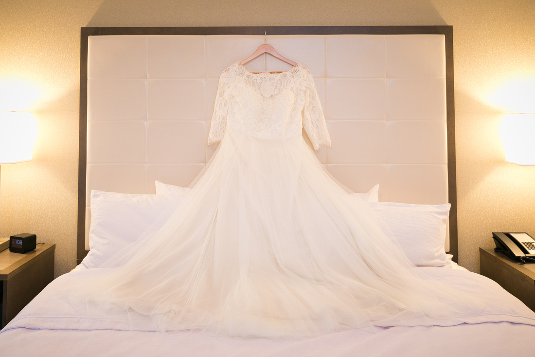 Wedding dress hangs on bed