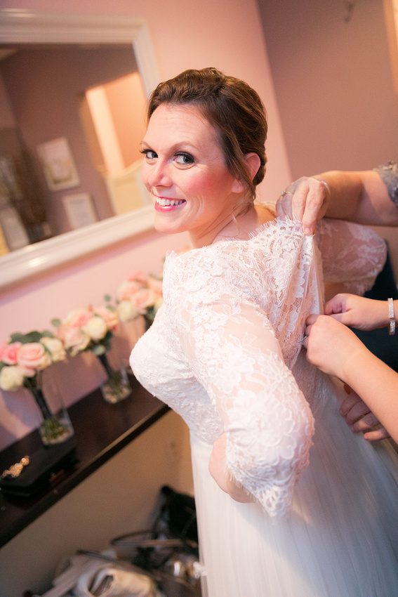 Bride gets wedding dress buttoned up