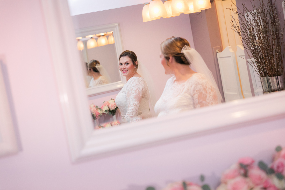 Bride poses looking in mirror