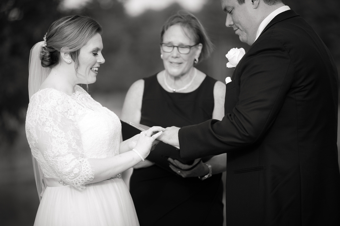 Bride puts wedding ring on groom's finger