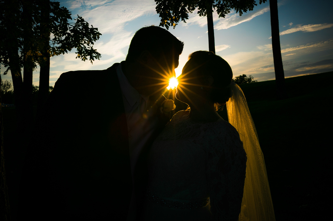 Couple silhouetted behind sun