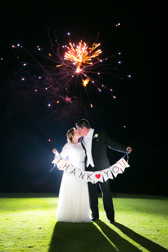 Bride and groom with sign and fireworks