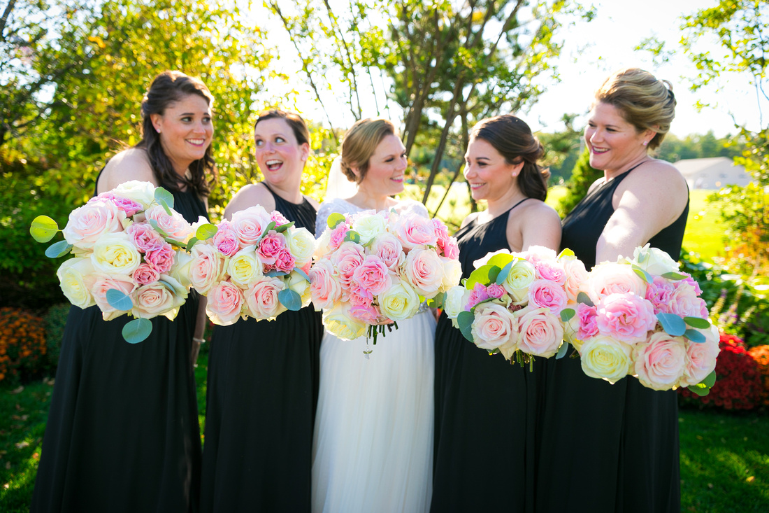 Bridesmaids hold out their bouquets