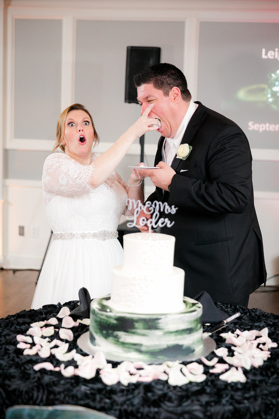 Bride feeds wedding cake to groom