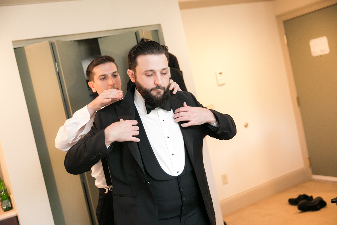 Best Man helps groom with jacket