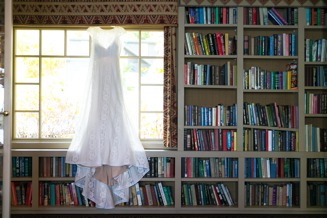 wedding dress hangs by books