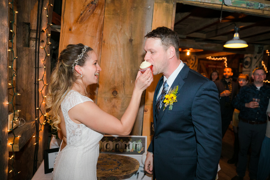 bride feeds groom a cupcake