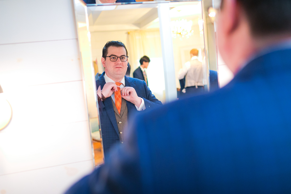 Groom adjusts tie in mirror