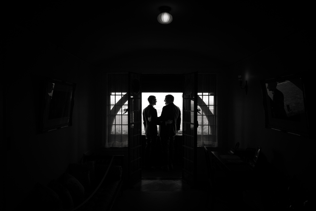 Silhouette of grooms kissing on balcony