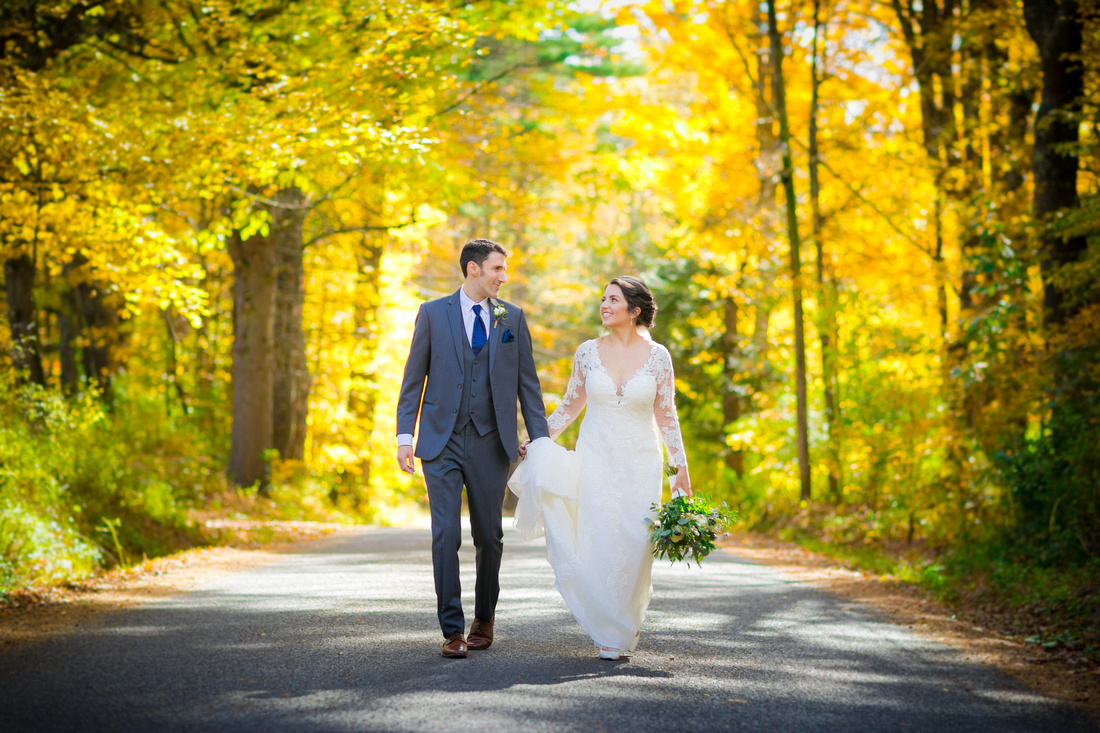 Bride and groom walk down road