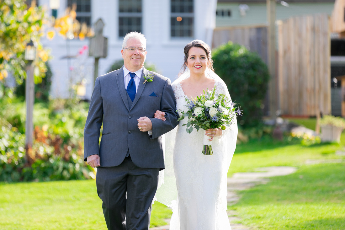 Bride and father walk towards ceremony