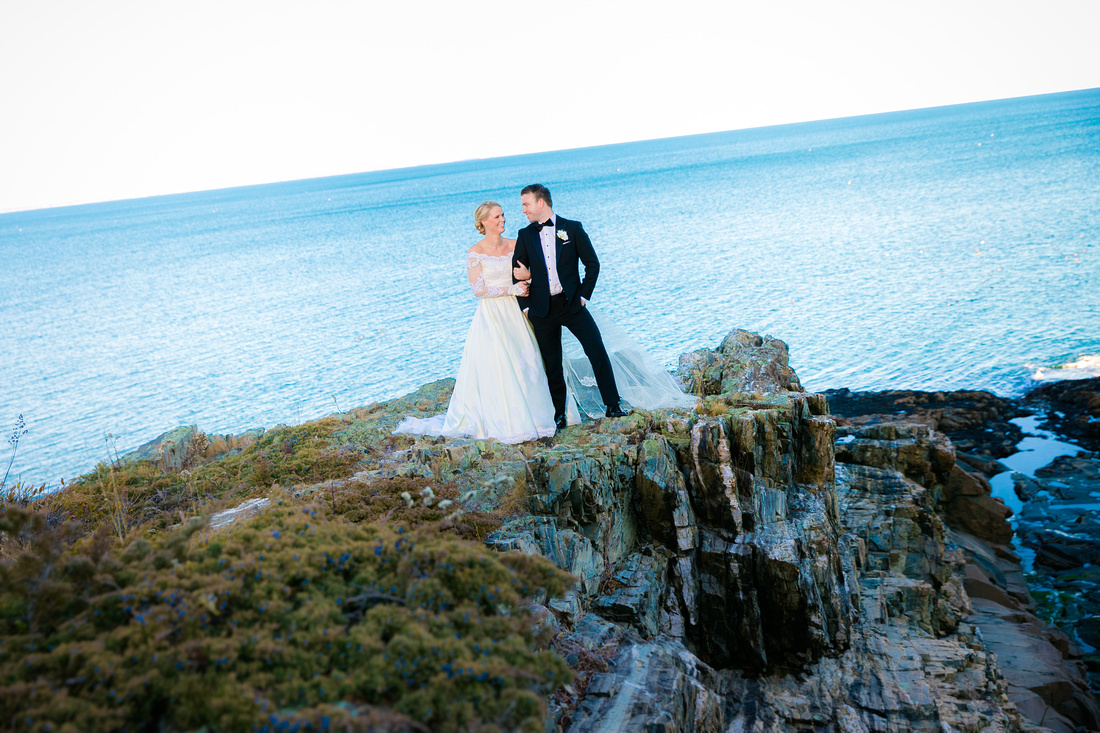 Bride and groom stand on rocks by ocean