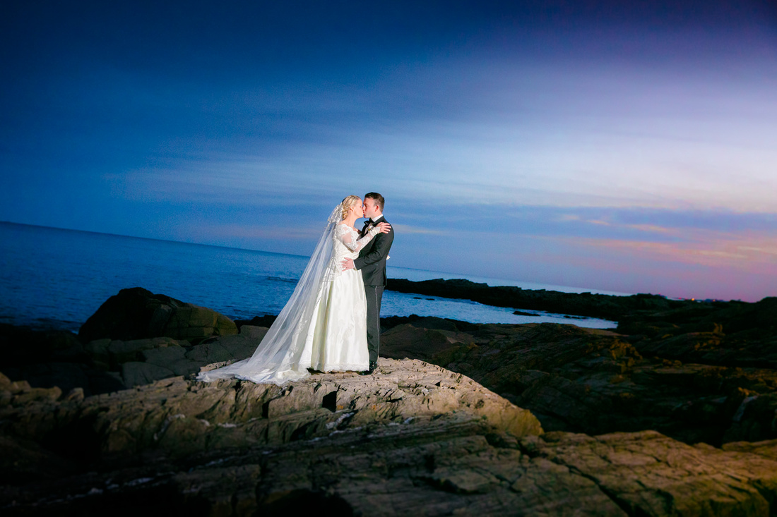 Bride and groom by ocean at sunset