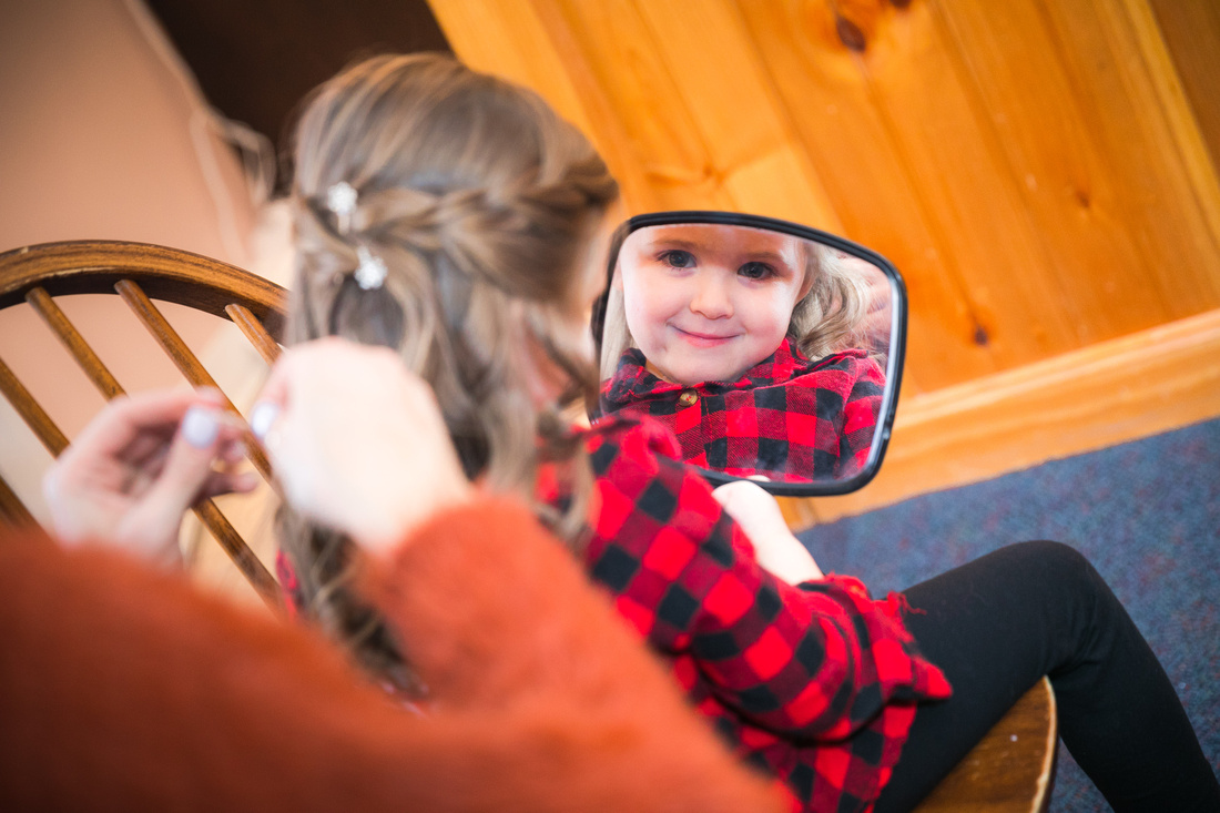 Flower girl smiles in mirror