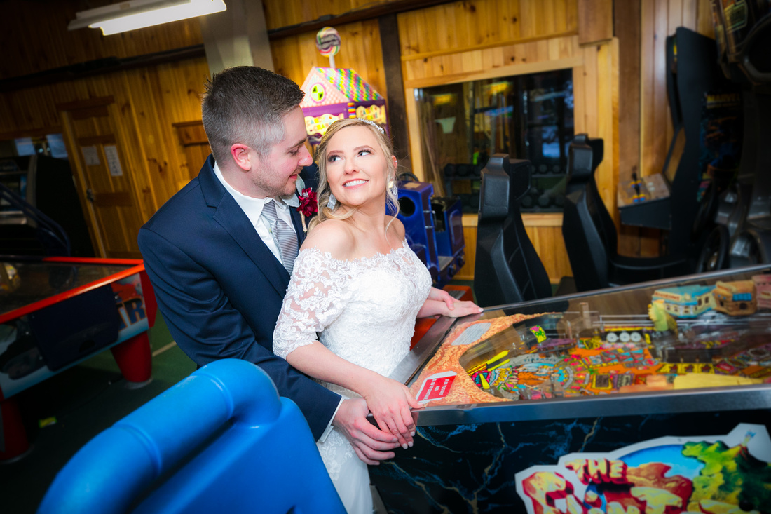 Bride and groom play pinball
