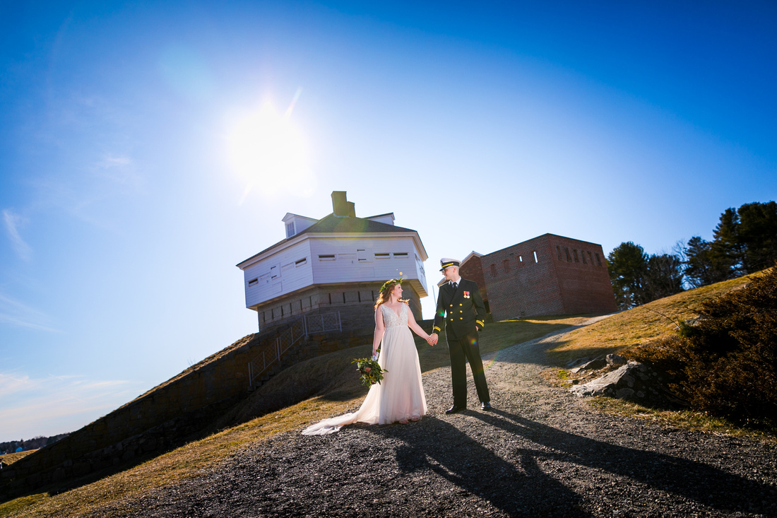 Bride and groom stand in front of fort McClary