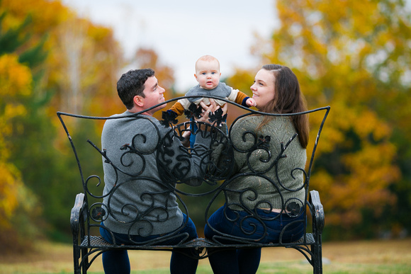 couple hold baby over iron bench