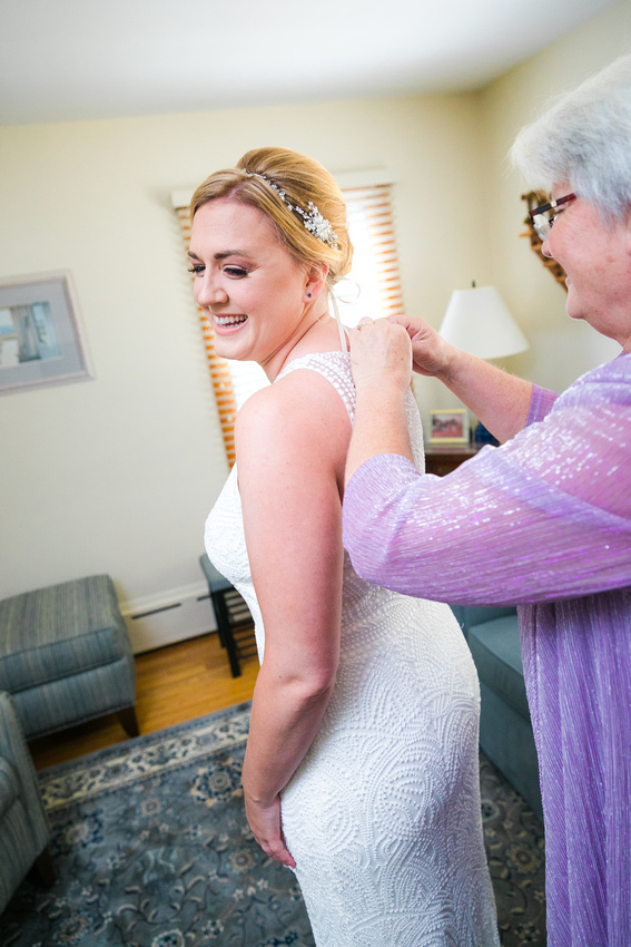 mom helps bride with wedding dress