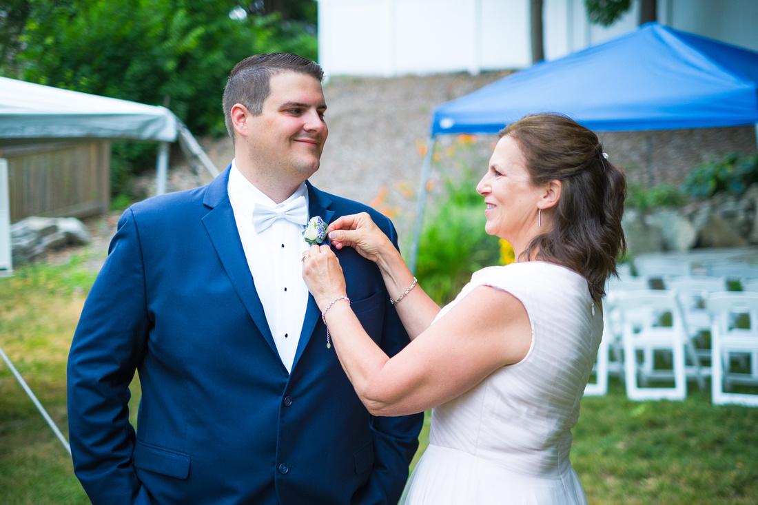 mom pins flower on groom