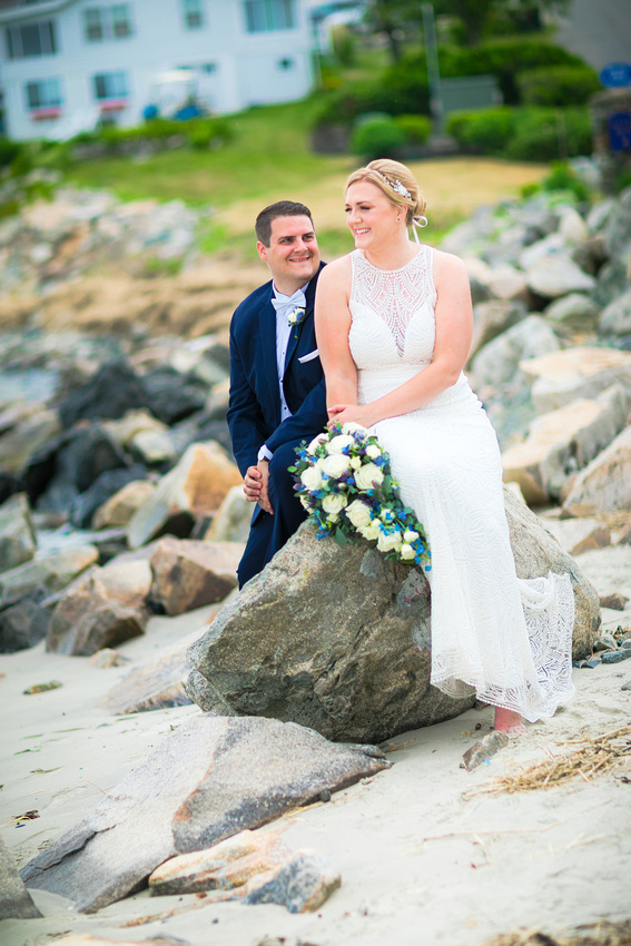 Bride and groom on rocky beach