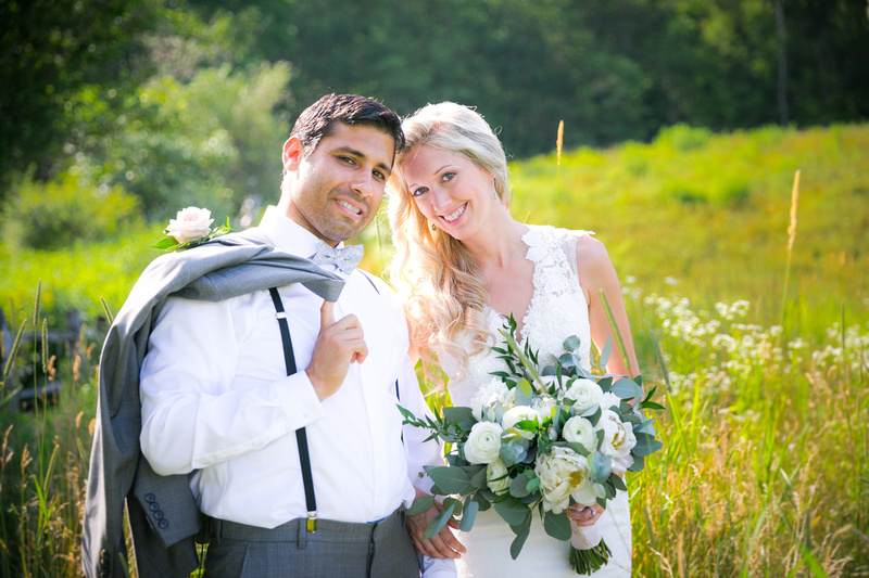Wedding couple in a field smiling to camera