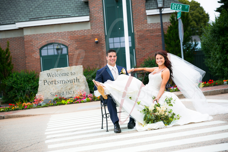 Wedding couple sit on a bench in the middle of the road